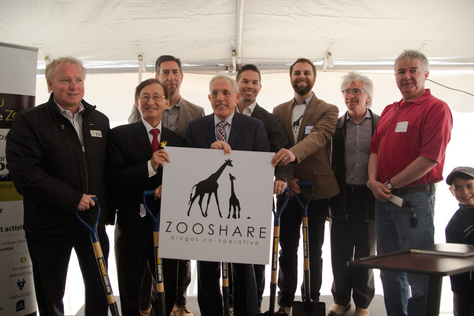 Group photo of speakers and dignitaries holding shovels and holding up ZooShare logo sign.