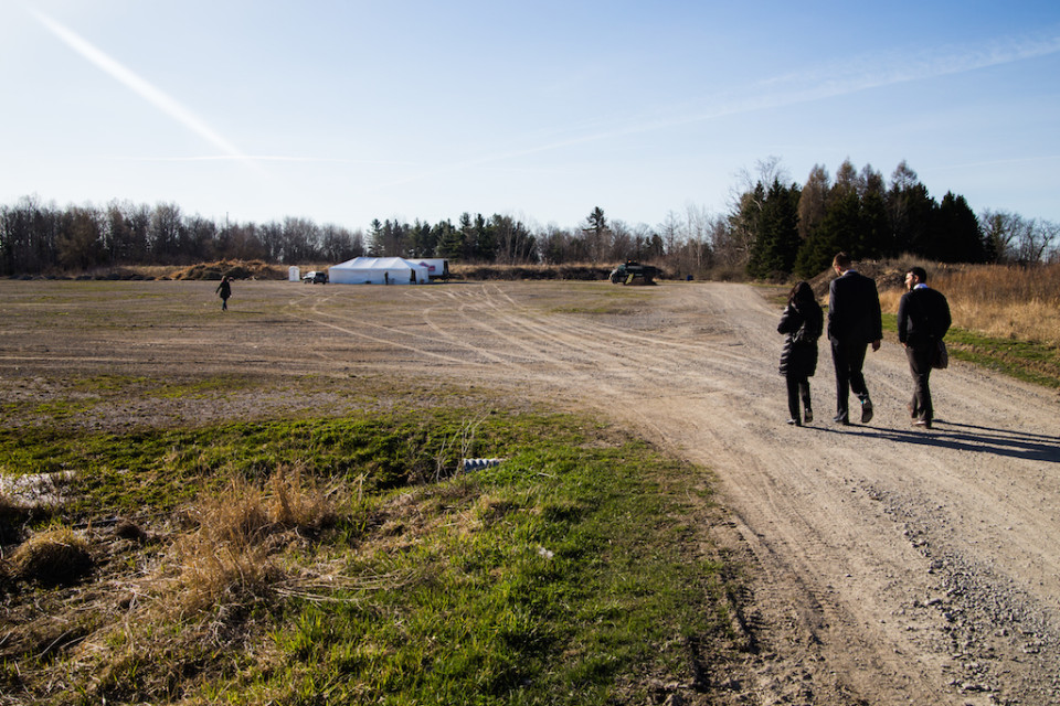 People walk to ZooShare groundbreaking ceremony, a large white tent is in the distance, across a dirt field.