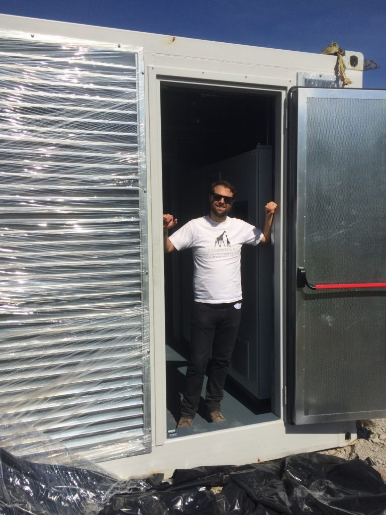 Executive Director Daniel Bida stands in the doorway of the shipping container that was used to deliver the ZooShare biogas plant engine.